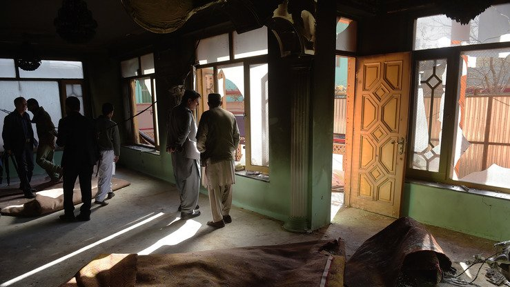 Afghans inspect the house of member of parliament Mir Wali in Kabul on December 22. Eight people were killed when Taliban suicide bombers stormed the residence, officials said. Security forces gunned down the attackers after a nearly 10-hour-long siege. [SHAH MARAI/AFP]