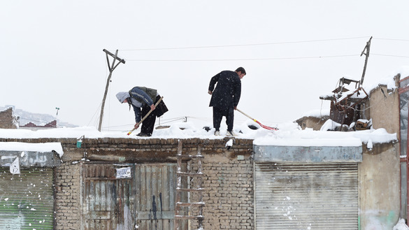 Afghan shopkeepers shovel snow off their roof in Kabul February 5. Three days of snowfall killed more than 100 people, mostly in Nuristan Province. [WAKIL KOHSAR/AFP]