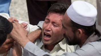 "A mourner (centre) weeps for those who were killed in a Kabul suicide bombing on July 23. The ""Islamic State of Iraq and the Levant"" (ISIL) claimed responsibility for the twin explosions targeting a Shia crowd. At least 80 Afghans were killed. [Shah Marai/AFP]"