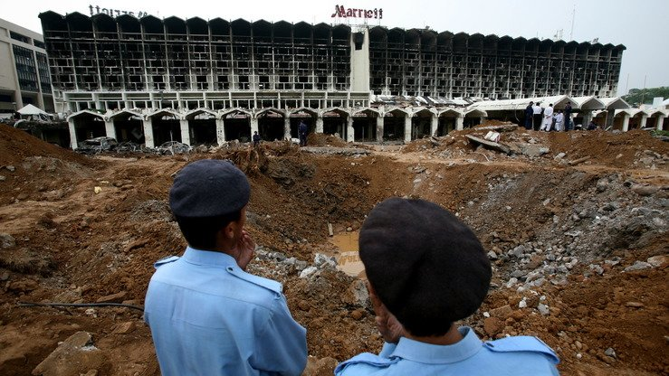 Pakistani policemen stand next to a crater left by a bomb blast next to the Marriott Hotel in Islamabad on September 22, 2008, two days after a suicide truck bombing destroyed the hotel. Qari Yasin is accused of being the mastermind behind this and many other attacks. [Pedro Ugartepedro/AFP]