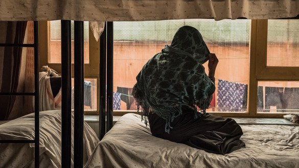 An Afghan woman looks out of the window of her bedroom at a women's shelter in Kabul March 20. The non-descript building is one of the few hidden sanctuaries where battered Afghan women can seek support. [Rebecca Conway/AFP]