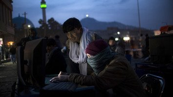 Afghanistan's Cyber Crime Law aims to block terrorist and militant groups' online activities among other crimes. In photo, a boy (seated) sells mobile phone apps in Kabul January 11, 2014. [AFP/Johannes Eisele]