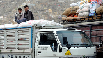 Afghan workers sit on consumer goods in the back of a truck in Kabul. Recently installed vehicle scanners at three entrances into the capital have given residents a sense of improved security. [Adek Berryadek Berry/AFP]