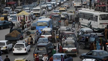 Pedestrians and commuters make their way through a Kabul rush hour August 29, 2012. Kabul is building a bus system to alleviate traffic woes. [Jose Cabezas/AFP]