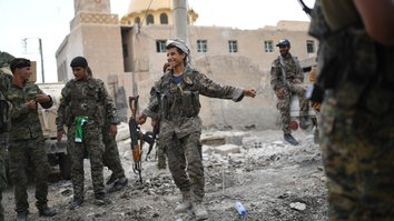 Members of the Syrian Democratic Forces dance as they hold a position on the eastern front line of Raqqa September 24. Syrian fighters backed by coalition forces are battling to clear the last remaining ISIS members holed up in their crumbling stronghold of a-Raqa. [Bulent Kilic/AFP]