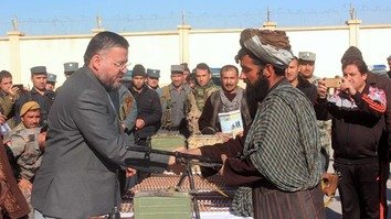 Jawzjan Governor Lutfullah Azizi (left) receives a weapon from one of nine former Taliban members who joined the peace process January 1 in Sheberghan, the provincial capital. [Sulaiman]