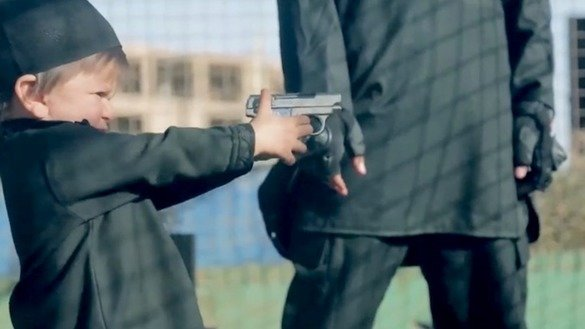 Screen shot from an ISIS video showing a militant giving a toddler a gun. Moments later in the video, the child shoots an 'apostate' to death.
