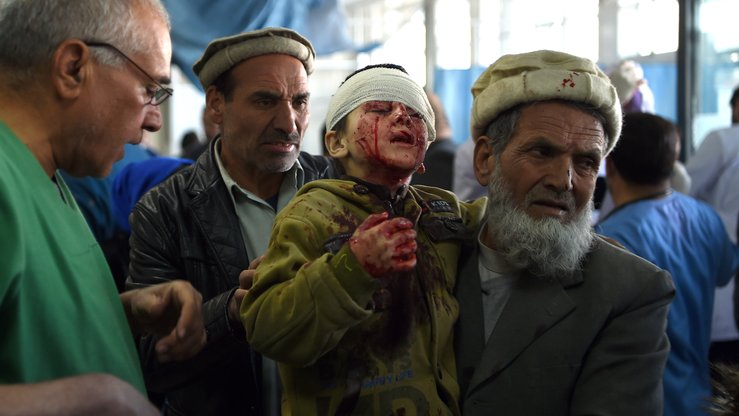 An Afghan man holds a wounded child after a massive bomb inside an ambulance exploded January 27 in Kabul. The Taliban claimed responsibility. [Wakil Kohsar/AFP]