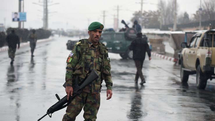 Afghan security personnel stand guard near the site of an attack near the Marshal Fahim Military Academy base in Kabul January 29. [Wakil Kohsar/AFP]