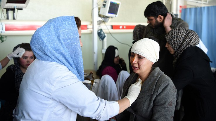 Afghan medics in Kabul treat a wounded woman after a car bomb exploded near the old Interior Ministry building January 27. More than 100 people were killed in the explosion, which the Taliban claimed. [Wakil Kohsar/AFP]