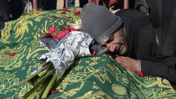 A relative reacts alongside the body of Saeed Jawad Hossini, 29, who was among seven killed in a Taliban suicide attack on a minibus carrying employees of Afghan TV channel TOLO in Kabul on January 21, 2016. Such attacks constitute war crimes and crimes against humanity, media and human rights groups say. [Shah Marai/AFP]