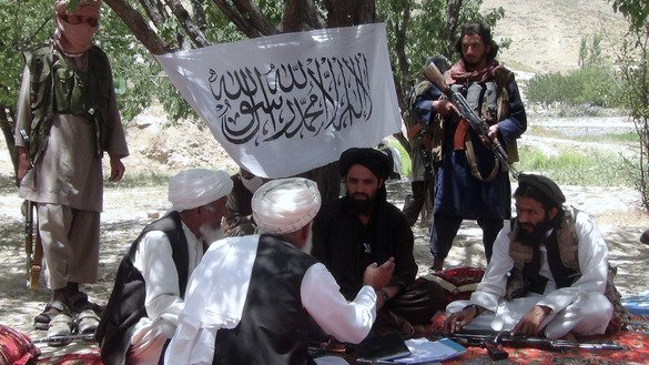 Taliban fighters talk with villagers in Ahmad Aba District on the outskirts of Gardez, Paktia Province, last July 18. [Faridullah Ahmadzai/AFP]