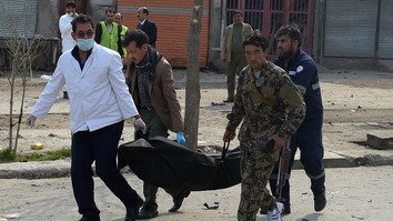 Afghan investigators carry the corpse of a suicide bomber who blew himself up in a Shia area of Kabul March 9. [Shah Marai/ AFP]