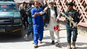 Afghans help an injured man following a bombing in Jalalabad March 19. [Noorullah Shirzada/AFP]
