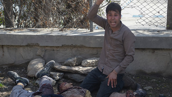 An Afghan man gestures beside dead bodies that were brought to a hospital following a suicide bombing in Kabul on March 21. The attack claimed by ISIS killed at least 26 people, many of them teenagers, in front of Kabul University, officials said, as Afghans took to the streets to celebrate Nawruz. [Shah Marai/AFP]