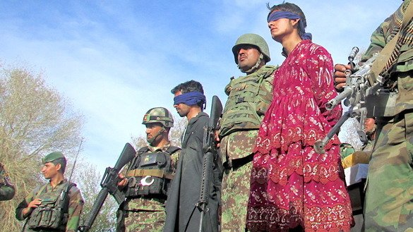 Afghan security forces present to the media three arrested Taliban fighters, including one wearing a dress, at Afghan National Army headquarters in Jalalabad March 17. [Khalid Zerai]