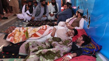 Afghan protesters lie down inside a tent in Lashkargah as they receive intravenous saline drips during a hunger strike March 31. Religious scholars have persuaded hunger strikers to resume eating, but the anti-Taliban demonstration continues with widespread support. [Noor Mohammad/AFP]
