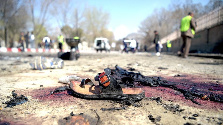 A sandal is seen laying on the ground along a road at the site of a suicide bombing in Kabul on March 21 amid Nawruz celebrations. The attack claimed by ISIS killed at least 26 people, many of them teenagers, in front of Kabul University, officials said. [Shah Marai/AFP]
