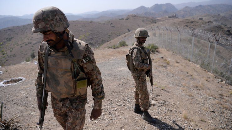 Pakistani soldiers patrol next to a newly fenced border separating North Waziristan and Afghanistan in October 2017. [Aamir Qureshi/AFP]