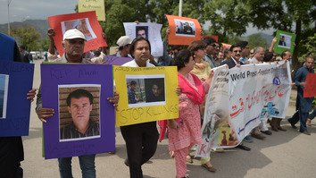 Pakistani local and foreign media personnel carry placards bearing images of slain Afghan journalists during a rally on World Press Freedom Day in Islamabad May 3. Ten Afghan journalists were killed April 30 in attacks that sparked outrage around the world and underscored the dangers faced by Afghan media. [Aamir Qureshi/AFP]