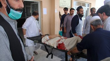 Afghans rush a wounded man to the hospital after a blast at a voter registration centre in Khost Province May 6. [Farid Zahir/AFP]