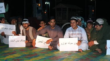 Members of the People's Peace Movement hold signs reading 'We want peace' at the sit-in in Lashkargah May 13. [Zia Samar]