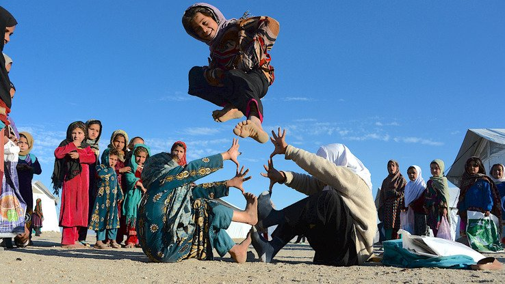 Afghan schoolgirls play at an open-air school in Laghman Province last December 23. Elders in Khost Province May 13 made education compulsory for girls and established a fine for anyone who prevents them from attending school. [Noorullah Shirzada/AFP]