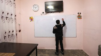 An adolescent boy writes on a whiteboard at the Hori rehabilitation centre for former 'Islamic State of Iraq and Syria' child fighters. [Delil Souleiman/AFP]