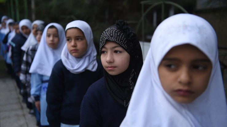 Afghan schoolgirls stand in line March 24 on the first day of the school year in the courtyard of a private school in Kabul. In Takhar Province, the Taliban shut down 27 schools -- depriving 11,000 children from education -- and threatened to kill educators and students. [Wakil Kohsar/AFP]