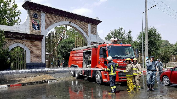 Afghan firefighters wash the road at the site of a suicide attack outside Kabul Polytechnic University in Kabul June 4. [Ahmad Zafar/AFP]