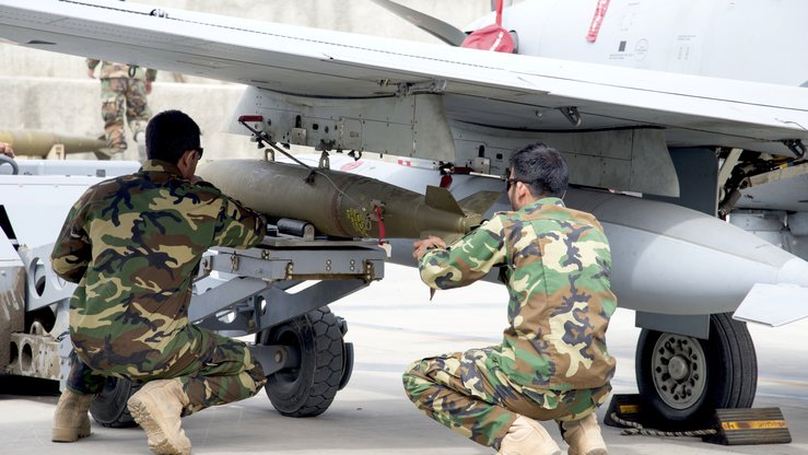 AAF A-29 maintainers manoeuvre a bomb in place before attaching it to an Afghan A-29 on March 6, at Kabul Air Wing. All training for AAF ammunition operations is conducted in the country by Afghans. [Staff Sgt. Jared J. Duhon/US Air Force]