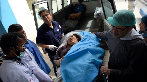 A wounded Afghan woman is transferred to an ambulance as she receives treatment at Isteqlal Hospital in Kabul after a suicide attacker blew himself up among Ministry of Rural Rehabilitation and Development employees June 11. [Wakil Kohsar/AFP]