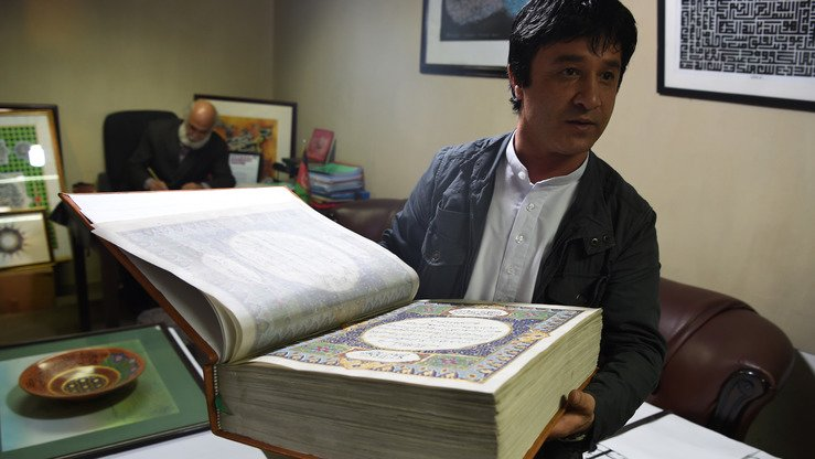 "Afghan master miniaturist Abdul Sabur Omari April 19 presents a handmade Koran made of silk at the Turquoise Mountain Foundation in Kabul. Such work is ""very rare"", said the foundation's director. [Wakil Kohsar/AFP]"