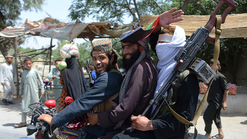Afghan Taliban militants ride a motorbike as they celebrate the second day of Eid in the outskirts of Jalalabad on June 16. Taliban fighters and Afghan security forces hugged and took selfies with each other in eastern Afghanistan during an unprecedented cease-fire during Eid. [Noorullah Shirzada/AFP]