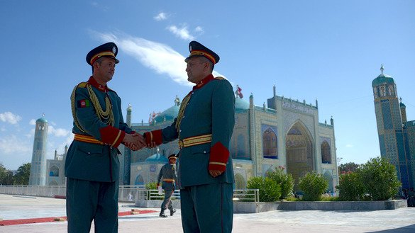Members of an honour guard greet each other June 15 after offering Eid ul Fitr prayers in Mazar-e-Sharif. [Farshad/Usyan/AFP]