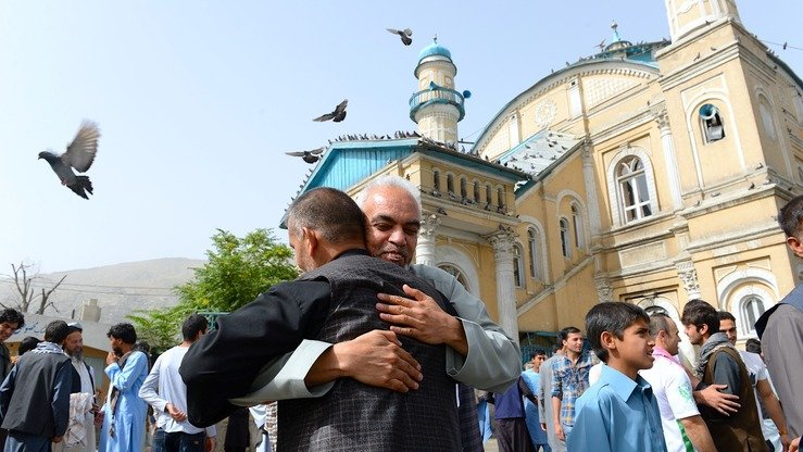 Muslims hug each other after offering prayers at the start of Eid ul Fitr at the Shah-e Do Shamshira mosque in downtown Kabul June 15. [Noorullah Shirzada/AFP]