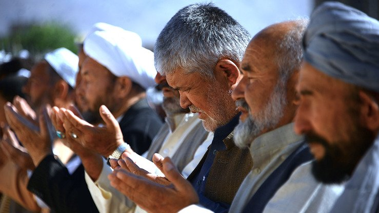 Men offer prayers June 15, the first day of Eid ul Fitr, in Herat Province. [Hoshang Hashimi/AFP]