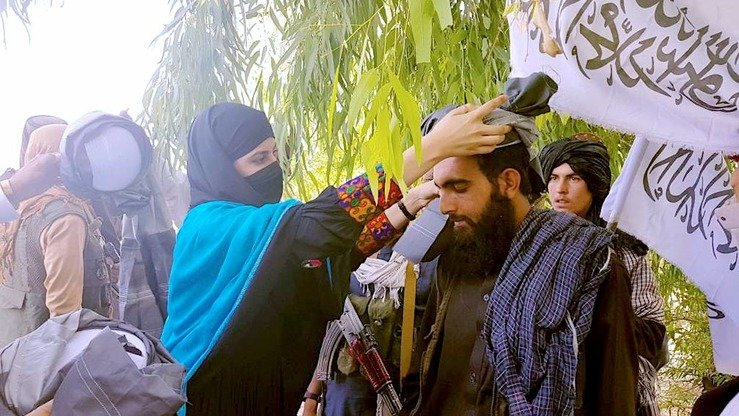 A woman places a turban on the head of a Taliban fighter as a traditional sign of respect and dignity in Nangarhar Province June 17. A number of women demanded that the militants extend the ceasefire beyond the three days of Eid ul Fitr. [Nangarhar Provincial Media Office/Facebook]