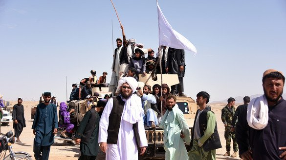 Taliban militants and local residents stand on an Afghan National Army (ANA) Humvee as they June 17 celebrate the unprecedented ceasefire on the third day of Eid ul Fitr in Maiwand District of Kandahar Province. [Javed Tanveer/AFP]