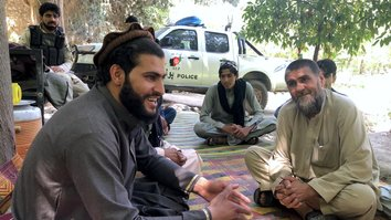 Zarqawi (left), a Taliban commander in Nangarhar Province, talks to local residents and Afghan security forces on June 16. He called the Eid ul Fitr ceasefire 'one of the good memories in my life'. [Khalid Zerai]