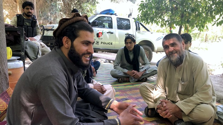 Zarqawi (left), a Taliban commander in Nangarhar Province, talks to local residents and Afghan security forces June 16. He called the Eid ul Fitr ceasefire 'one of the good memories in my life'. [Khalid Zerai]