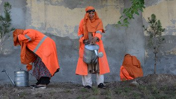 Female municipality employees water a garden in Jalalabad April 23. [Noorullah Shirzada/AFP]