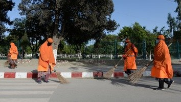 Female municipality employees sweep a street in Jalalabad April 23. [Noorullah Shirzada/AFP]