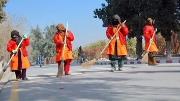 Women sweep a street in Jalalabad January 15. They received their jobs through a Nangarhar Province employment programme for those who lost loved ones in terrorist attacks. [Khalid Zerai]