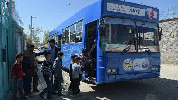 Afghan children board a mobile library bus in Kabul April 4. The library on wheels offers pupils and street children free access to children's books, which are scarce at public schools and libraries. [Shah Marai/AFP]