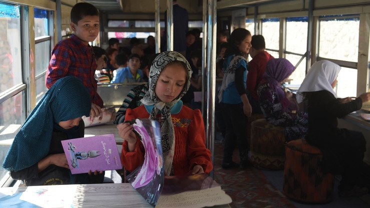 Afghan children read books in a mobile library bus in Kabul April 4. [Shah Marai/AFP]