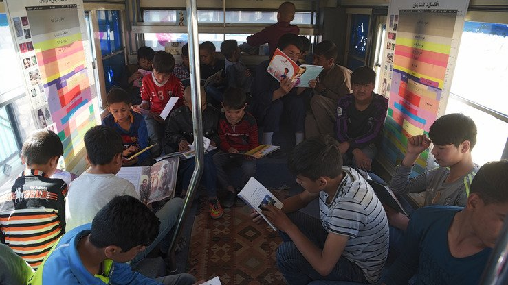 Afghan youths read books in a mobile library bus in Kabul April 4. [Shah Marai/AFP]