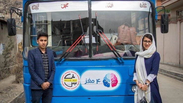 Charmaghz founder Freshta Karim (right) poses in front of the library on wheels May 12. Karim said she hopes to raise donations to rent another two buses. [Charmaghz/Facebook]