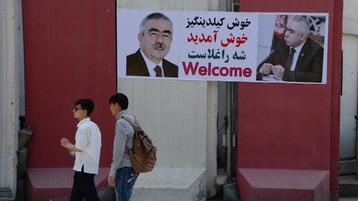 Pedestrians walk past a banner with the image of self-exiled First Vice President Gen. Abdul Rashid Dostum ahead of his arrival in Kabul July 22. [Noorullah Shirzada/AFP]
