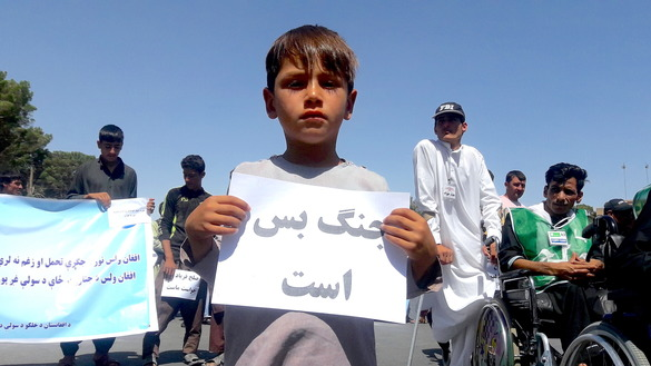 A child carries a sign reading 'no more war' in Herat city July 21. [Nasir Salehi]